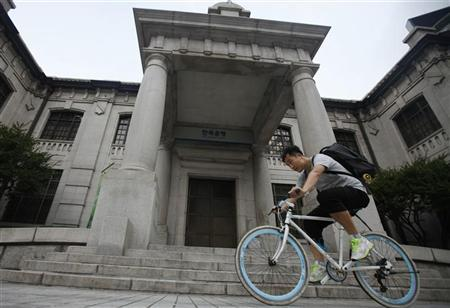 A man gets on a bicycle in front of the Bank of Korea in Seoul August 9, 2012. REUTERS/Kim Hong-Ji