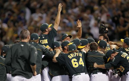 Oakland Athletics players celebrate after defeating the Texas Rangers to earn a wild card berth during their MLB American League baseball game in Oakland, California October 1, 2012. REUTERS/Robert Galbraith