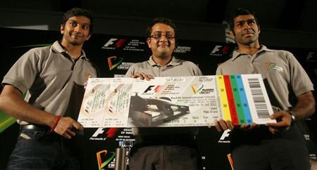 Formula One drivers Narain Karthikeyan (L) and Karun Chandhok (R) pose with Sameer Gaur, managing director and chief executive of race promoters JPSI, as they display a ticket of the first Indian Grand Prix before a news conference on the outskirts of Delhi August 20, 2011. REUTERS/Parivartan Sharma