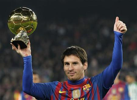 Barcelona's player Lionel Messi of Argentina shows his FIFA Ballon d'Or 2011 trophy to his supporters before their Spanish First division soccer match against Betis at Camp Nou stadium in Barcelona January 15, 2012. REUTERS/Albert Gea