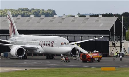 A fire crew attends to the Boeing 787 Dreamliner, owned by Qatar Airways, after a fire started in the ground power unit beneath, but not a part of, the plane at the Farnborough Airshow 2012, in southern England July 11, 2012. REUTERS/Luke MacGregor