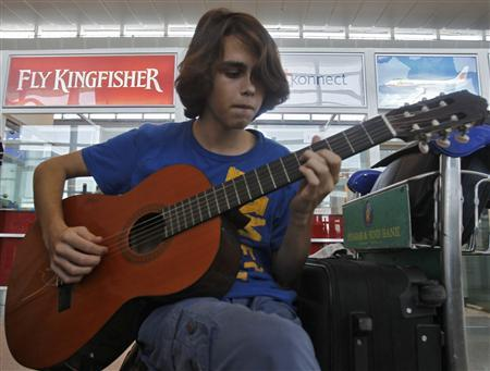 A stranded tourist plays the guitar in front of a Kingfisher Airlines' counter at an airport in New Delhi October 1, 2012. REUTERS/Mansi Thapliyal