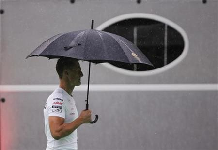 Mercedes Formula One driver Michael Schumacher of Germany walks through the paddock as it rains ahead of the first practice session of the Singapore F1 Grand Prix at the Marina Bay Street Circuit September 21, 2012. REUTERS/Tim Chong