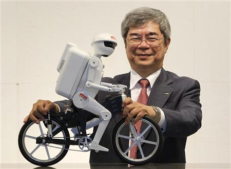 Murata Manufacturing Co Ltd President Tsuneo Murata poses with his company's bicycle-riding robot ''Murata Seisaku-kun'' after an interview with Reuters on the sidelines of CEATEC JAPAN 2012 electronics show in Chiba, east of Tokyo, October 2, 2012. REUTERS/Yuriko Nakao