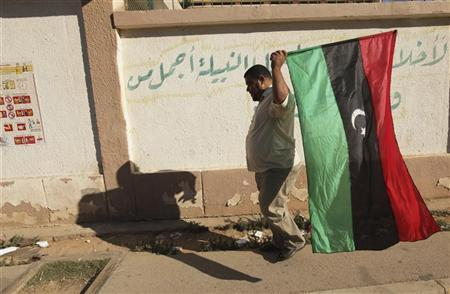 A man carries a Kingdom of Libya flag as he goes to vote in the National Congress election, in Benghazi July 7, 2012. REUTERS/Esam Al-Fetori