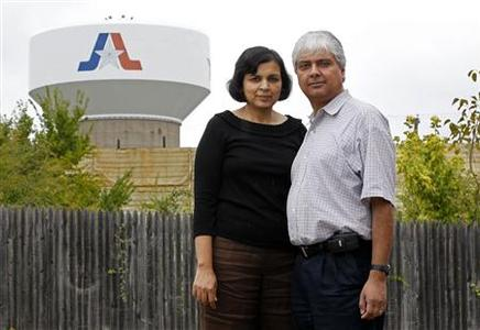 Ranjana Bhandari and her husband Kaushik De, who recently failed in their attempt to prevent Chesapeake Energy from drilling for gas near their home, stand near a Chesapeake Energy gas well in Arlington, Texas September 16, 2012. Picture taken September 16, 2012. REUTERS/Mike Stone