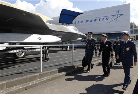 A Danish delegation walks pass Lockheed Martin's F-35 Lightning II, at the Farnborough Airshow in southern England July 11, 2012. REUTERS/Luke MacGregor