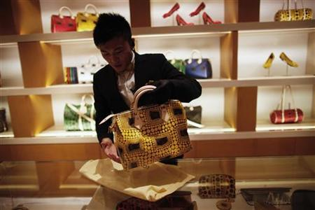 A Louis Vuitton vendor shows a bag to a customer during Vogue's 4th Fashion's Night Out: Shopping Night in downtown Shanghai September 7, 2012. REUTERS/ Carlos Barria