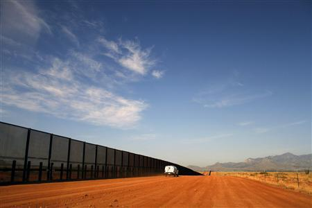 A U.S. Border vehicle drives along the U.S. and Mexico border fence in Naco, Arizona, in this September 7, 2011 file photo. REUTERS/Joshua Lott/Files