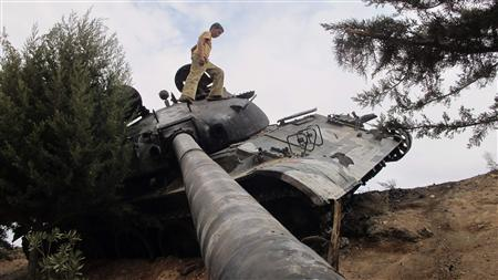 A boy walks on a damaged Syrian Army tank, belonging to forces loyal to Syria's President Bashar al-Assad, near Idlib October 2, 2012. REUTERS/Abdalghne Karoof