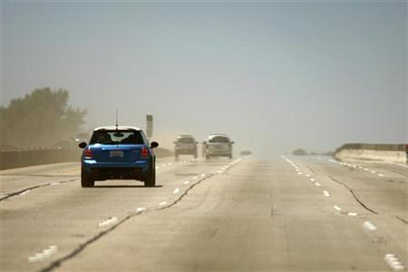 Cars pass through the dust on a freeway in Los Angeles, California July 17, 2011. REUTERS/David McNew