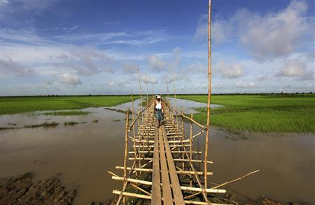 People walk on a wooden bridge at the Thilawa economic zone outside Yangon October 2, 2012. REUTERS/Soe Zeya Tun