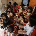 Liza Cabiya-an, a 39-year-old housewife with 14 children aged between 22 and 11 months, eats bread dipped in coffee, with some of her children at a cramped shanty in Manila September 12, 2012. Pitting himself against the teachings of the country's powerful Catholic church, Philippine President Benigno Aquino, a Catholic like 80 percent of the population, has thrown his support behind a reproductive health bill that will, if passed, guarantee access to free birth control and promote sex education. Picture taken September 12, 2012. REUTERS/Erik De Castro