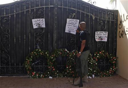 A Libyan government militia guarding the main entrance of the U.S. consulate that was attacked last week, fixes a note written by Libyans against the attack, in Benghazi city September 18, 2012. REUTERS/Asmaa Waguih