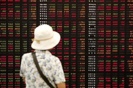 An investor looks at an electronic board showing stock price index at a stock brokerage firm in Seoul July 1, 2009. REUTERS/Jo Yong-Hak