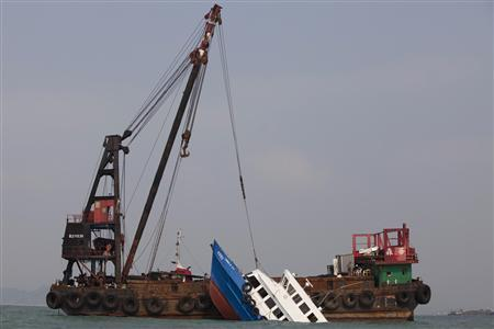 A sunken ferry is lifted out of the water after a collision off Hong Kong October 2, 2012. REUTERS/Tyrone Siu