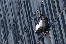 A worker cleans windows on a building in London January 5, 2011. REUTERS/Stefan Wermuth
