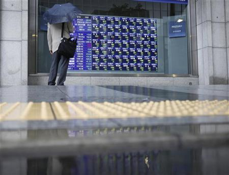 A man looks at an electronic monitor displaying share prices outside a brokerage in Tokyo August 19, 2011. REUTERS/Yuriko Nakao/Files