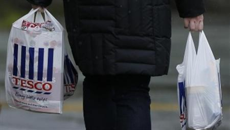 A Shopper carries bags as she leaves a Tesco store near Manchester, northern England April 18, 2012. REUTERS/Phil Noble