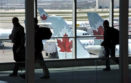 Passengers walk past Air Canada planes on the runway at Pearson International Airport in Toronto April 13, 2012. REUTERS/Mike Cassese