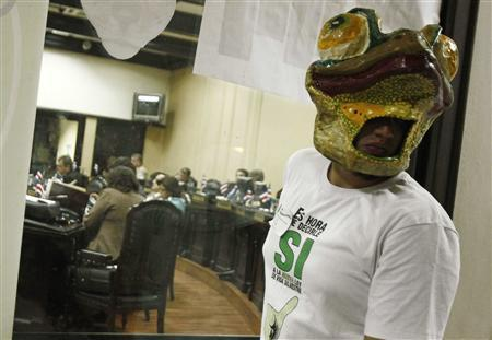An environmentalist wearing a frog mask is seen near members of Congress (rear) who are voting on an anti-hunting law inside the Legislative Assembly building in San Jose October 1, 2012. REUTERS/Juan Carlos Ulate