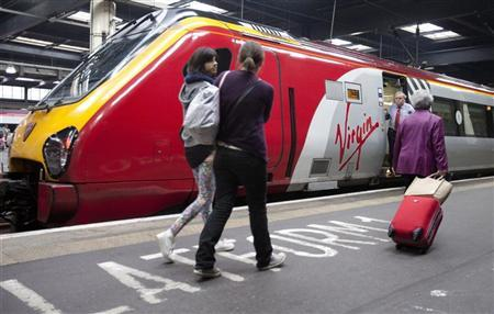 Travellers walk to a Virgin train at Euston rail station in London August 15, 2012. REUTERS/Neil Hall