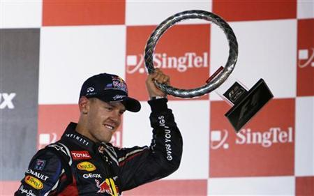 Red Bull Formula One driver Sebastian Vettel of Germany holds his trophy as he celebrates his win in the Singapore F1 Grand Prix at the Marina Bay Street Circuit in Singapore September 23, 2012. REUTERS/Edgar Su