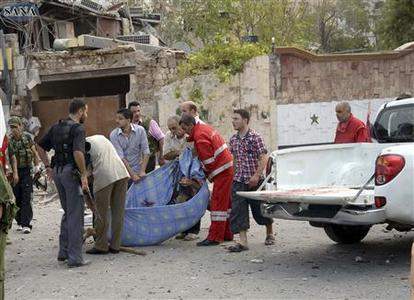 Men carry a victim, after blasts ripped through Aleppo's main Saadallah al-Jabari Square, October 3, 2012, in this handout photograph released by Syria's national news agency SANA. REUTERS/SANA