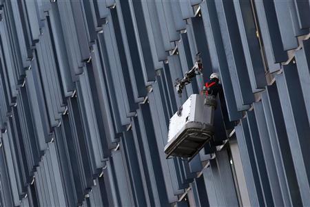 A worker cleans windows on a building in London January 5, 2011. REUTERS/Stefan Wermuth