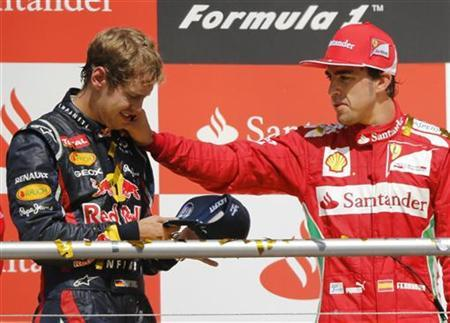 Red Bull Formula One driver Sebastian Vettel of Germany looks at his cap as Ferrari's winner Fernando Alonso of Spain (R) gestures at the Hockenheimring in Hockenheim July 22, 2012. REUTERS/Wolfgang Rattay/Files