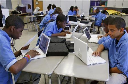 Students at the Lilla G. Frederick Pilot Middle School work on their laptops during a class in Dorchester, Massachusetts June 20, 2008. REUTERS/Adam Hunger