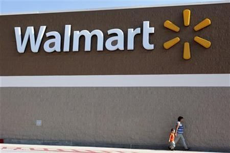 People walk past a Wal-Mart sign in Rogers, Arkansas June 4, 2009. Wal-Mart Stores Inc said on Thursday that its strong financial position leaves it well positioned to take advantage of acquisition opportunities across the globe. REUTERS/Jessica Rinaldi