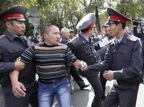 Полицейские задерживают демонстранта на акции протеста в столице Киргизии Бишкеке 3 октября 2012. Полицейские столкнулись с по меньшей мере 2.000 демонстрантов, некоторые из которых попытались взять штурмом здание парламента Киргизии в среду. REUTERS/Vladimir Pirogov