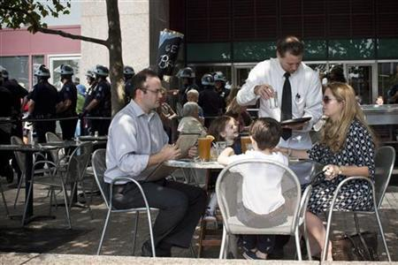 A family is served drinks at a restaurant while Occupy Wall Street activists protest through the streets of New York's Financial District on the one-year anniversary of the movement, in New York September 17, 2012. REUTERS/Andrew Burton