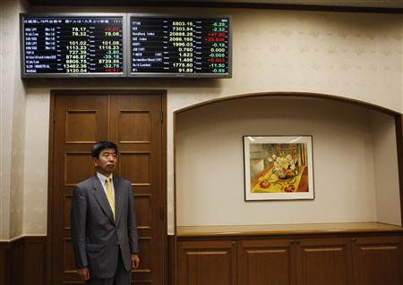 Takehiko Nakao, Japan's vice finance minister for international affairs, poses for a picture below a screen showing markets information during an interview with Reuters at his office at the finance ministry in Tokyo October 3, 2012. REUTERS/Issei Kato