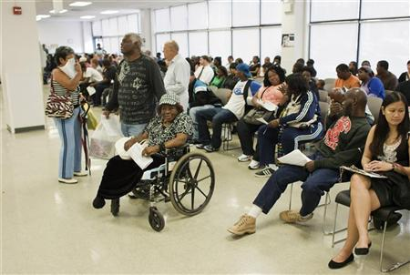 Larry Johnson (C) stands next his mother Ethel, 87, sitting in her wheelchair as they wait to get a voter ID card inside a Pennsylvania Department of Transportation office in Philadelphia September 27, 2012. REUTERS/Tom Mihalek