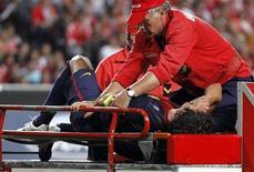 Carles Puyol, do Barcelona, é retirado do campo em maca após sofrer lesão em jogo contra o Benfica, durante partida da Liga dos Campeões no estádio Luz, em Lisboa. 02/10/2012 REUTERS/Jose Manuel Ribeiro