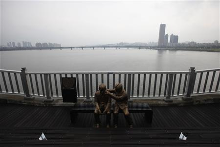 A statue of a person comforting another is seen on the Mapo Bridge, one of 25 bridges over the River Han in Seoul in this September 28, 2012 picture. REUTERS/Kim Hong-Ji
