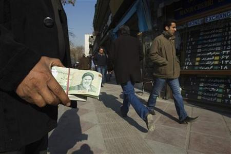 A money changer holds Iranian rial banknotes as he waits for customers in Tehran's business district January 7, 2012. REUTERS/Raheb Homavandi