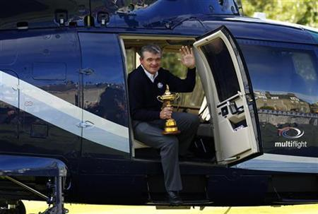 Europe Ryder Cup team golfer Paul Lawrie waves to the media as he steps out of a helicopter holding the Ryder Cup in the grounds of the Gleneagles Hotel, the venue for the 2014 Ryder Cup, in Scotland October 3, 2012. REUTERS/David Moir