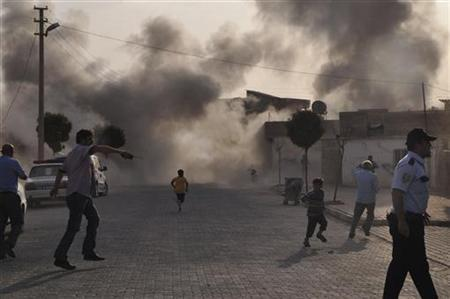 Smoke rises over the streets after an mortar bomb landed from Syria in the border village of Akcakale, southeastern Sanliurfa province, October 3, 2012. REUTERS/Rauf Maltas/Anadolu Agency