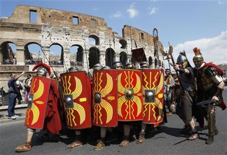 Members of the Gruppo Storico Romano (Roman Historical Group) dressed as centurions perform as they march past the ancient Colosseum in Rome, to mark the 2,764th anniversary of the founding of the city April 17, 2011. REUTERS/Alessandro Bianchi