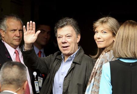 Colombian President Juan Manuel Santos (C) waves to the media with his wife Maria Clemencia upon his arrival at a hospital for surgery in Bogota October 3, 2012. REUTERS/Presidency/Handout