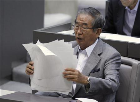 Tokyo Governor Shintaro Ishihara organises his documents after delivering a policy speech about the territorial dispute over the uninhabited group of islands in the East China Sea -- known as the Senkaku in Japan and Diaoyu in China, under flags of Japan and Tokyo at Tokyo metropolitan assembly in Tokyo September 19, 2012. REUTERS/Yuriko Nakao