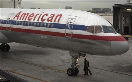 A worker walks underneath an American Airlines airplane at Miami International airport in Miami, Florida November 29, 2011. REUTERS/Lucas Jackson