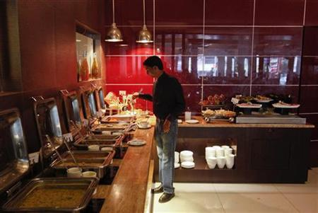 A guest looks at the buffet in a restaurant at the Keys Hotel Nestor in Mumbai May 3, 2012. REUTERS/Vivek Prakash/Files