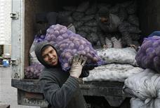 Таджикские гастарбайтеры разгружают грузовик с картошкой на овощном рынке в Москве, 11 ноября 2011 года. Азиатский банк развития (АБР) повысил прогноз роста валового внутреннего продукта Таджикистана по итогам текущего года на 1 процентный пункт до 6,5 процента, приняв во внимание значительный прирост потока денежных переводов таджикских гастарбайтеров на родину, сообщило представительство АБР в четверг. REUTERS/Denis Sinyakov