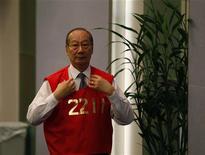 Трейдер Гонконгской биржи поправляет форму, 8 августа 2012 года. Азиатские фондовые рынки завершили торги разнонаправлено под влиянием местных факторов. REUTERS/Bobby Yip