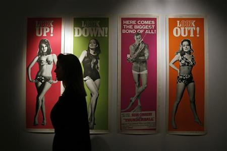 A worker walks past a complete set of original cinema door panel posters from the film ''Thunderball'', during a media preview of ''50 Years of James Bond - the Auction'', at Christie's in London September 28, 2012. The set is estimated to sell for 5,600 - 7,400 GBP ($9,100-12,000) at an online-only auction from September 28 to October 8. REUTERS/Stefan Wermuth