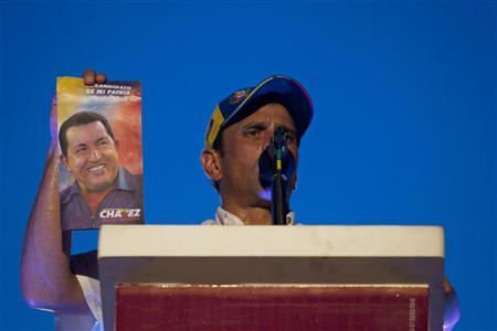Venezuela's opposition presidential candidate Henrique Capriles holds a copy of the government proposals of Venezuela's President Hugo Chavez as he talks to supporters during a campaign rally in Maracay, about 100 km (62 miles) west of Caracas September 26, 2012. REUTERS/Carlos Garcia Rawlins
